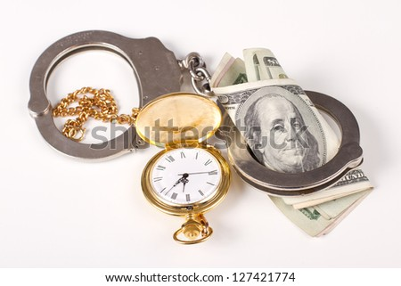 concept of doing jail time for money, handcuffs and time and money over a white background - stock photo