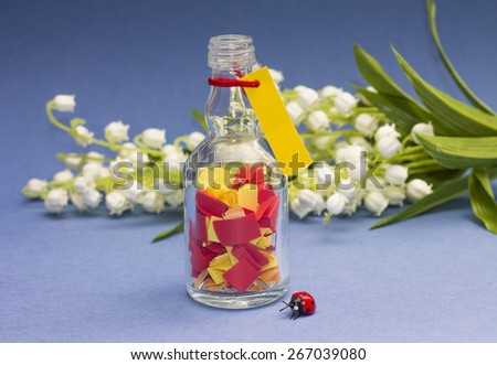 Concept of dreams. Bottle with colorful papers, on blue background - stock photo