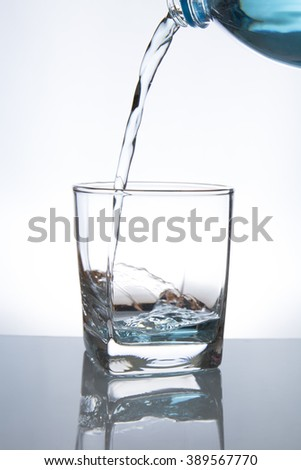 Concept of drinking. Pouring water from into glass - stock photo