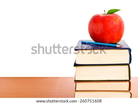 Concept of education. A red apple and pencil sitting on top of a stack of school books. - stock photo