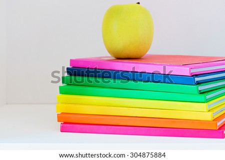 Concept of education. A yellow apple sitting on top of a stack of school books - stock photo