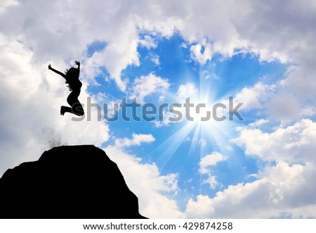Concept of emotions and feelings. Silhouette of happy woman jumping on a mountain top - stock photo