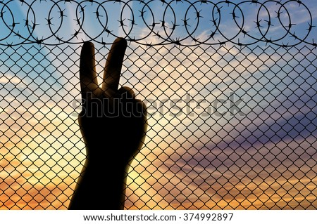 Concept of emotions and feelings. Silhouette refugee arms near the border fence on the sunset background