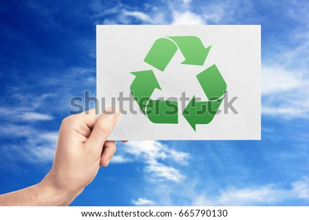 Concept of environmental conservation and protection. Man holding paper with symbol of recycling on sky background