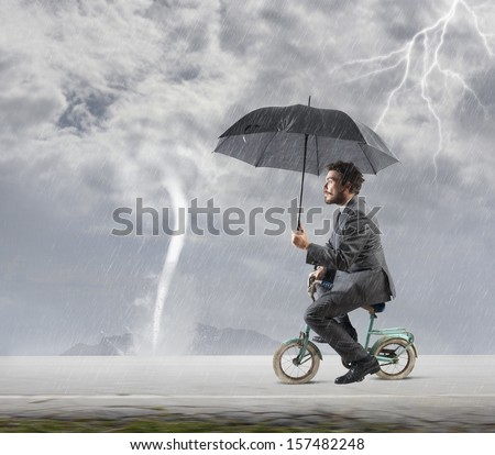 Concept of escape from crisis with businessman on bike - stock photo