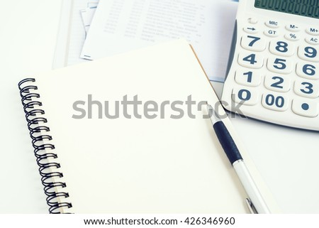 Concept of expenses and personal payment, open notebook with pen, calculator, and bills - stock photo