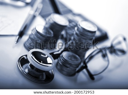Concept of expensive healthcare with coins and stethoscope. Tinted in blue.