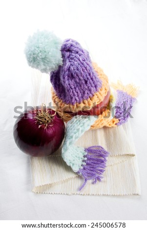 Concept of flu sick person with cap and scarf with healthy tea, fruit and vegetable
