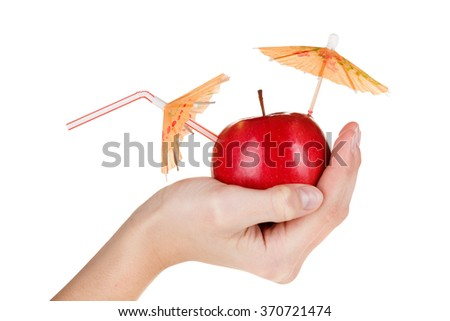 Concept of fresh apple juice featuring an apple with a straw and umbrella  in hand isolated on white background.  - stock photo