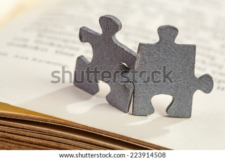 Concept of friendship and learning: closeup of two jigsaw puzzle pieces on a book page. Shallow depth of field - stock photo