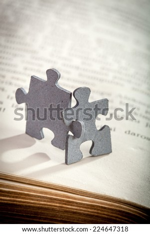 Concept of friendship and learning: closeup of two jigsaw puzzle pieces on a page of  book. Shallow depth of field - stock photo