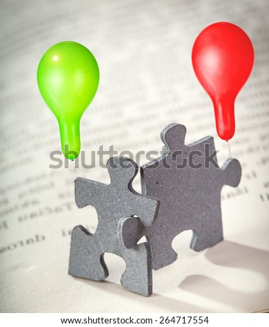Concept of friendship: closeup of two jigsaw puzzle pieces on a page of  book holding green and red balloons. Shallow depth of field - stock photo
