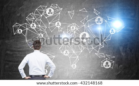 Concept of global social network with businessman looking at abstract polygonal map and people icons on chalkboard background