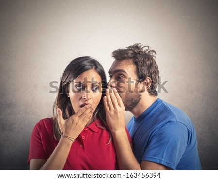 Concept of gossip with boy whispers girl - stock photo