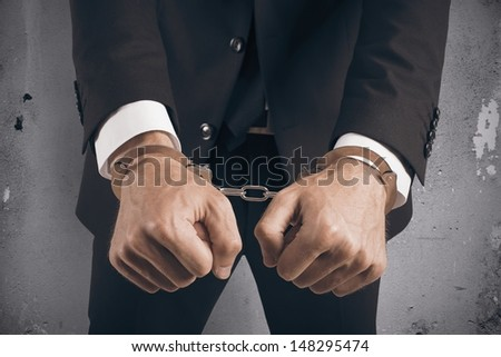 Concept of handcuffed businessman in jail - stock photo