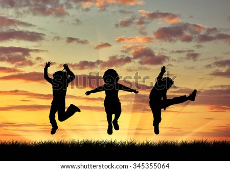 Concept of happiness. Silhouette happy children jumping at sunset
