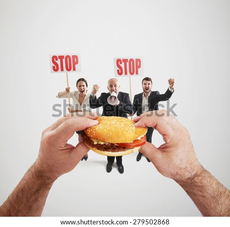 concept of harmful fast foods. small people screaming and holding placard with stop sign, big hands holding fat burger and ready to eat it - stock photo