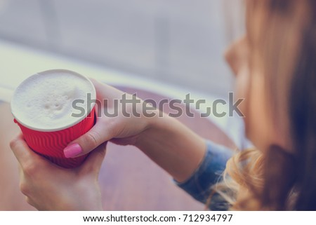 Concept of having a cup of coffee in the morning. Young lady is gossiping with her best friend in a cafe while drinking frothy coffee. Close up photo of coffee with foam. Top, overhead view