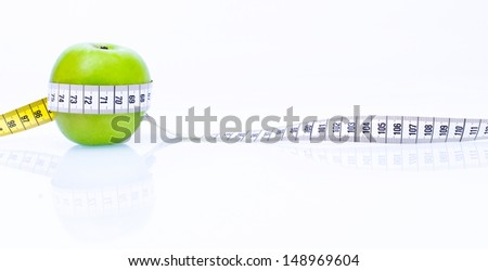 Concept of health apple with measuring tape on reflecting white background
