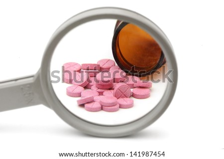 concept of health problems with bottle of pills and magnifier - stock photo