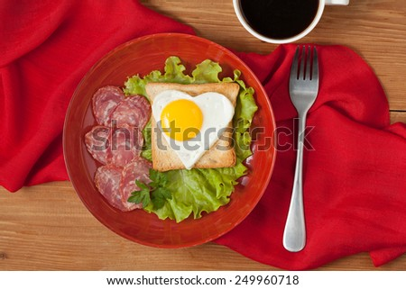 Concept of healthy breakfast or lunch with love - fried heart-shaped egg on toast with salad and sausage for Valentines Day or Easter - stock photo