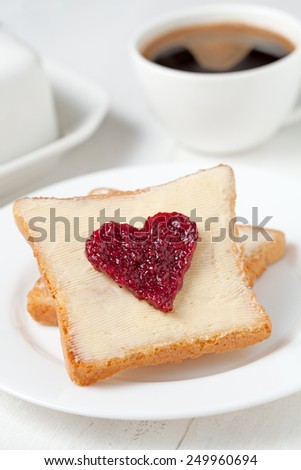 Concept of healthy breakfast - slices of wholewheat toast with red berry jam in the shape of heart with coffee - stock photo