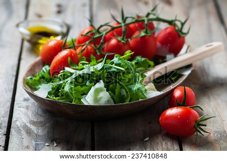 Concept of healthy italian food with arugula, tomato and cheese, selective focus