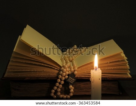 Concept of knowledge. Open book, candle and necklace pearl. Focus on pearls.