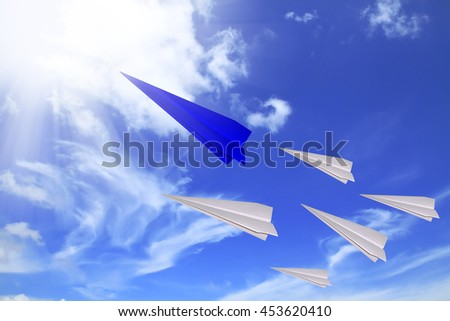 Concept of leadership as paper plane flying to the rising sun