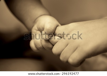 concept of love and family. hands of father and baby closeup