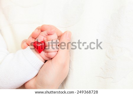 concept of love and family. hands of mother and baby closeup - stock photo