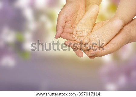 concept of love and family. mothers hand holding babies little feet,