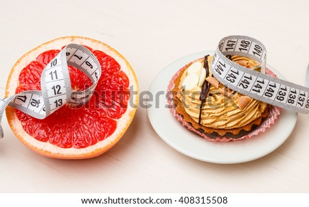 Concept of making choice: healthy low-calorie or unhealthy high-calorie food, slimming or fattening. Grapefruit and cake cupcake with measuring tape - stock photo