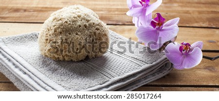 concept of massage and washing-up with natural sponge and orchid flowers for wellbeing - stock photo