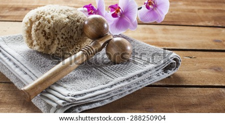 concept of massage and washing-up with towel, natural sponge, wooden accessory and orchid flowers for relaxation - stock photo