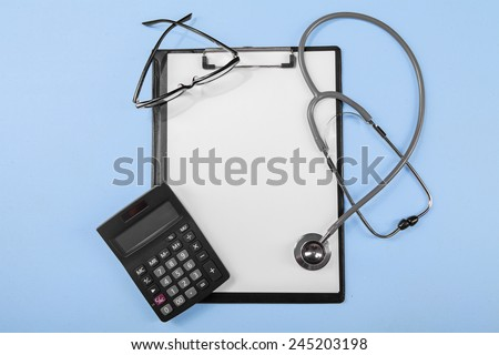 Concept of medical cost with calculator, clipboard, glasses, and stethoscope - stock photo