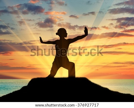 Concept of meditation and relaxation. Silhouette of a girl practicing yoga class on a background of sea sunset