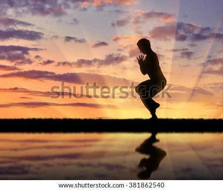 Concept of meditation and relaxation. Silhouette of a man practicing yoga at sunset and reflection in water