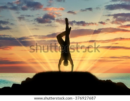 Concept of meditation and relaxation. Silhouette of a man practicing yoga class on a background of sea sunset