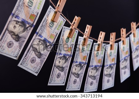 Concept of money laundering - one hundred bills hanging on a cord against grey background - stock photo