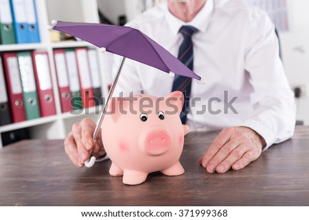 Concept of money protection with umbrella over a piggy - stock photo