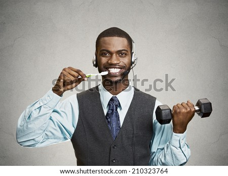 Concept of multitasking businessman. Closeup portrait corporate business man talking on phone, brushing teeth, lifting dumbbell isolated grey wall background. Face expression, emotion. Phone addiction - stock photo
