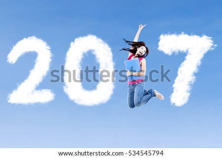 Concept of New Year 2017. Cheerful female college student jumping on the blue sky with clouds shaped number 2017