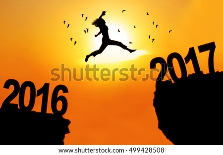 Concept of New Year 2017. Silhouette of a young woman jumping between 2016 and 2017 above cliff