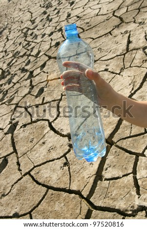 concept of of water shortage - a hand with an empty bottle on the background of dried ground - stock photo