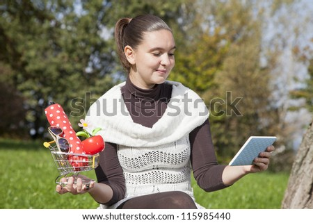 Concept of on line shopping- cute girl thinks what to shop online- with tablet PC and shopping trolley - stock photo