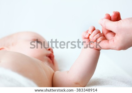 concept of parental love. newborn baby hand holding  finger of mother - stock photo