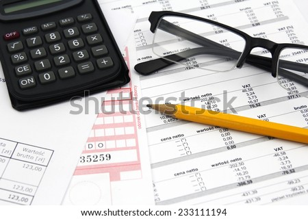 concept of paying bills- glasses, calculator and pencil on paper - stock photo