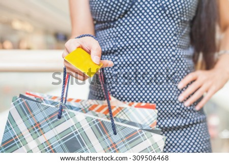 Concept of payment by plastic card at big shopping centre. Close-up of woman's hand holding credit card and bags with purchases - stock photo
