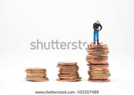 Concept of poor man saving. Poor man  searching coin in pocket standing on coin stack.
